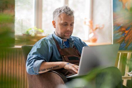 Serious painter in workwear sitting in studio in front of laptop display Stock fotó