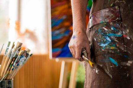 Hand of contemporary artist in apron holding paintbrush while working in studio