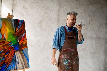 Cheerful middle aged painter in workwear recording voice message on smartphone