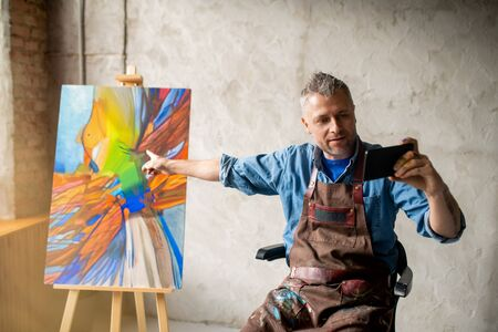 Modern painter with smartphone pointing at artwork on easel in studio