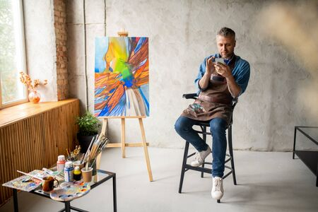 Casual painter with smartphone sitting in studio and scrolling in mobile phone