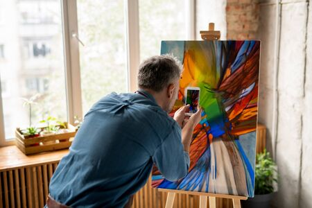 Contemporary man with smartphone taking photograph of the painting on easel Banco de Imagens