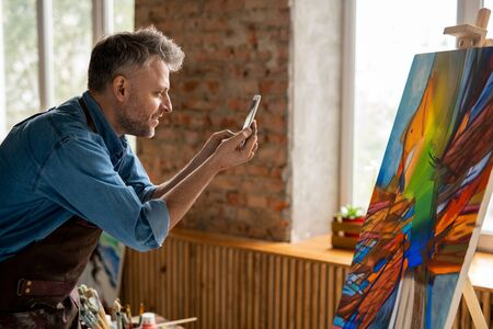 Side view of happy mid-aged artist with smartphone taking photo of artwork