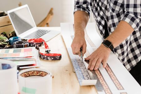 Young casual craftsman with knife and ruler bending over table while cutting decorative workpieces for creative pet collars