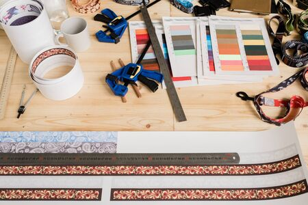 Ruler on paper with set of decor, samples of textile, mug with drink and other stuff for accessory design on wooden table