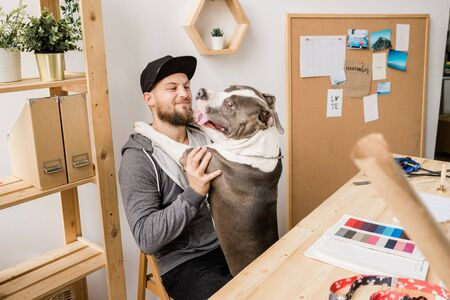 Happy young casual man sitting on chair by wooden table and playing with his pet