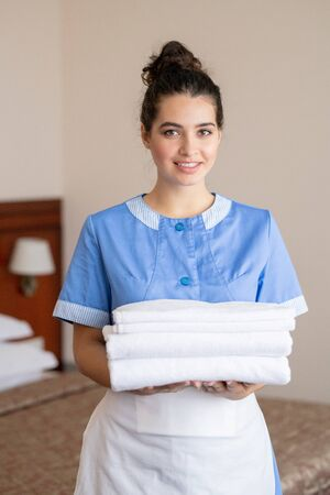 Pretty girl in blue uniform and white apron looking at you while holding towels