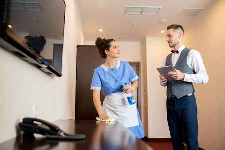 Pretty young room maid with detergent talking to porter in corridor of hotel Stock fotó