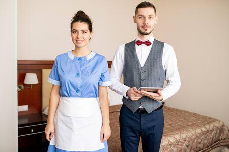 Happy young chamber maid in uniform and elegant porter with touchpad