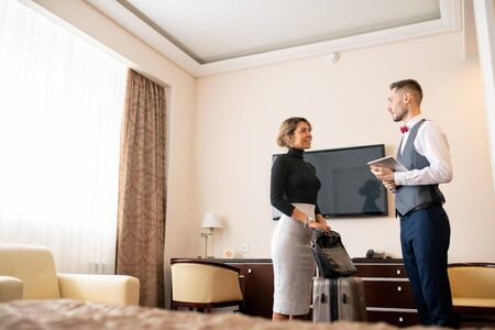 Young elegant porter with touchpad talking to pretty businesswoman with baggage Stock fotó