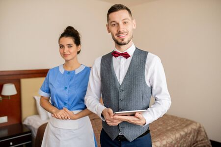 Young successful porter and pretty chamber maid in uniform Stock fotó