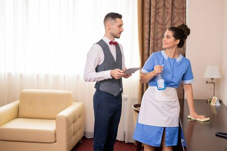 Pretty room maid cleaning table while looking at porter during conversation