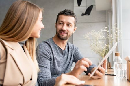Happy young businessman with tablet and his colleague consulting at meeting