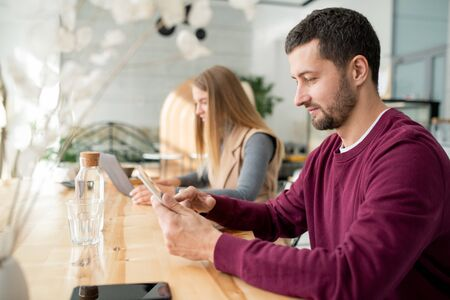 Contemporary young man scrolling in digital tablet while having rest in cafe