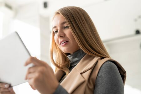 Young confident businesswoman with touchpad watching online course or webinar