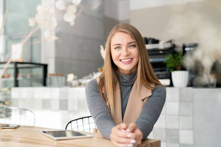 Happy girl in smart casual sitting by table in cafe in front of camera Stock fotó