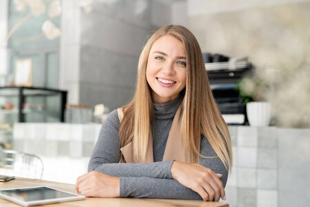 Happy young blond busineswoman in smart casualwear relaxing in cafe