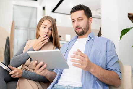 Young worried couple looking at touchpad display while surfing in the net