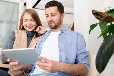 Young restful affectionate couple with tablet relaxing in cafe at leisure