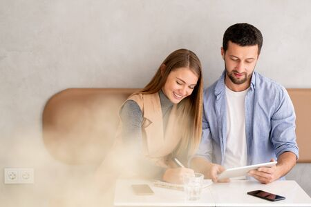 Happy young businesswoman making working notes with colleague near by Stock fotó