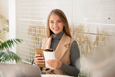 Young cheerful businesswoman with toothy smile spending time in cafe