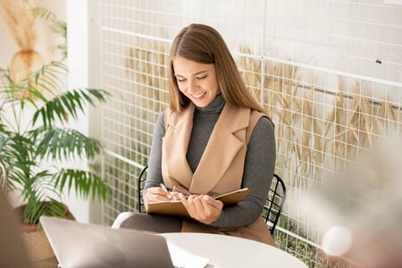 Student or businesswoman with notebook and pen making notes in front of laptop