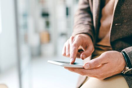 Hands of young elegant businessman pointing at smartphone screen or scrolling through information