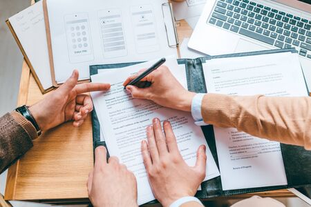 One of business partners pointing at contract while his colleague putting personal data before signing the document Stock Photo