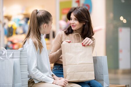 Young female with paperbag looking at her daughter while discussing purchase Stock Photo