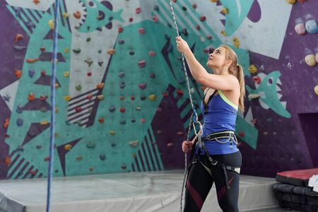 Young female climbing instructor holding safety rope while standing by wall