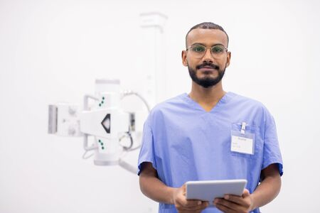 Young bearded mixed-race intern in uniform and eyeglasses using touchpad 版權商用圖片