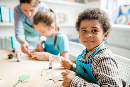 Cute schoolboy in blue apron preparing handmade carton halloween decorations