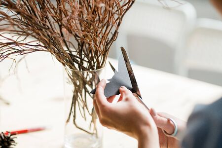 Hands of woman cutting paper bat with scissors to decorate dry branches in glass Stock Photo
