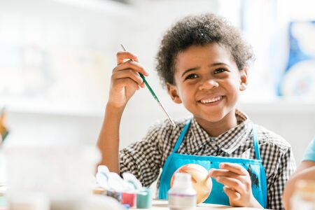 Cheerful schoolboy with paintbrush making Christmas toy ball at lesson Stock Photo