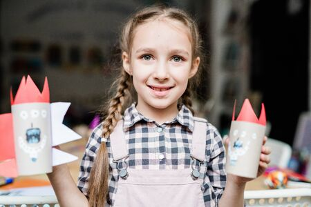 Cute smiling schoolgirl showing scary halloween toys made up of rolled paper