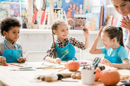 One of naughty schoolgirls in blue aprons hit the other with pinecone at lesson Stock fotó