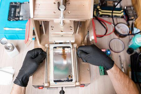 Repairman using equipment for gadget repair while examining broken smartphone