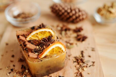 Handmade soap bar with aromatic spices and orange slices surrounded by other ingredients on table