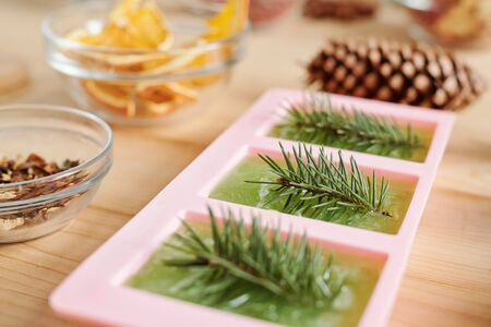 Handmade green soap with conifer and glassware with aromatic ingredients Stock Photo