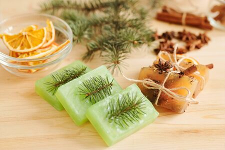 Fresh handmade soap bars scented by conifer and aromatic spices on table Stock Photo