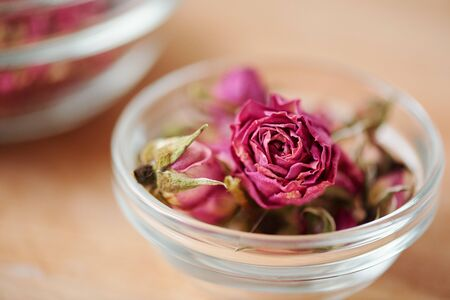 Dry pink rosebud in small glassware that can be used in process of soap making standing on table