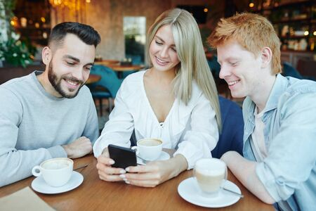 Pretty young smiling woman and two happy guys watching video in smartphone Archivio Fotografico - 133482561
