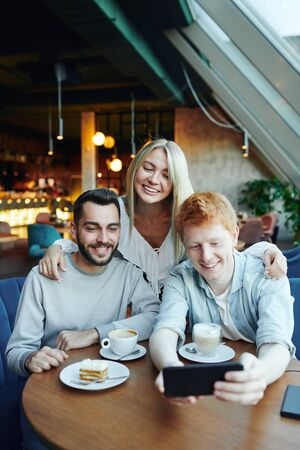 Group of happy young affectionate friends making selfie on smartphone in cafe