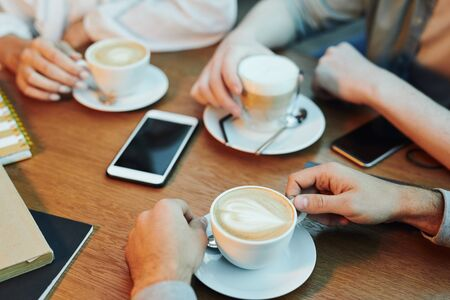 Hands of friends gathered by wooden table in cafe and having cappuccino Archivio Fotografico - 133482582