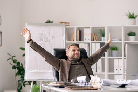 Happy architect with raised arms sitting by desk in office and enjoying break Stock Photo