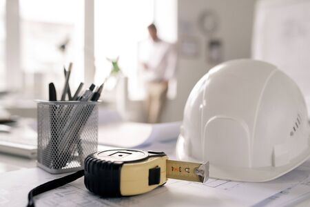 Workplace of engineer with hardhat, measuring tape, bunch of pencils and sketch