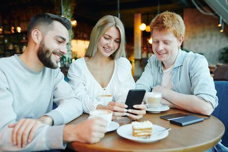 Pretty blonde girl with smartphone showing two happy guys her new photos in cafe