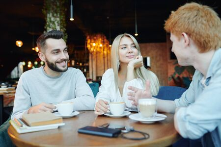 Happy young heterosexual couple chatting to their friend by cup of cappuccino Archivio Fotografico - 133482653