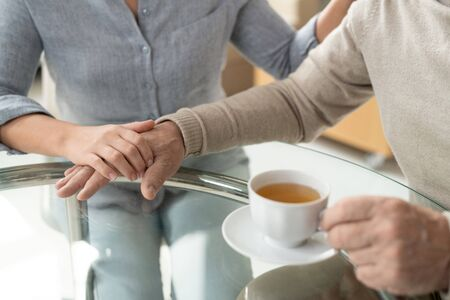 Careful young daughter holding hand of her retired aged father having cup of tea by table after lunch Archivio Fotografico - 133484515