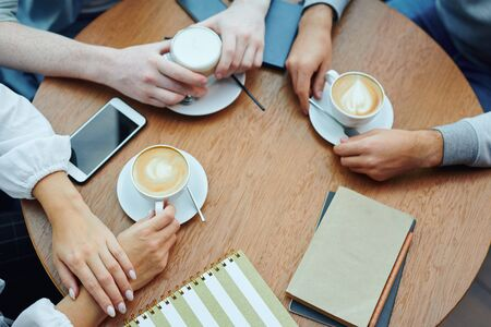 Overview of hands of college students with gadgets and drinks gathered by table in cafe for cup of cappuccino and chat Archivio Fotografico - 133484828